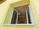 Síť proti holubům před oknem panelového domu