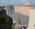 Konstrukce zabezpečující napnutí sítě na stříšce nad balkónem